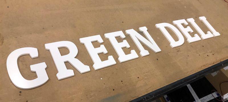 Enseigne en PVC blanc pour un restaurant parisien GREEN DELI